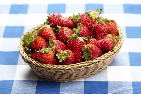 Basket of strawberries on checkered tablecloth Imagens