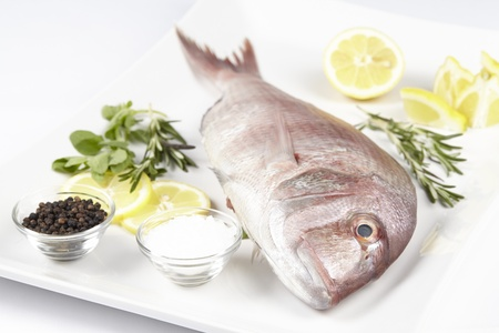 A red sea bream, coarse salt, black pepper, lemon slices and pieces, oregano and rosemary