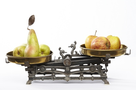 Apples and pears on an old balance exempted on a white background   Stock Photo
