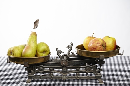 blackwhite: Apples and pears on an old balance  The balance is located on a black-white checkered tablecloth