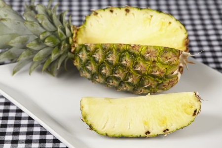 blackwhite: A cutted pineapple on a porcellain plate  The plate is located on a black-white checkered tablecloth