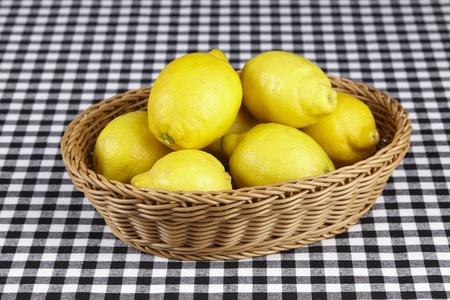A basket of lemons on a black and white tablecloth.