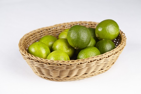 exempted: A basket of limes exempted on a white background.