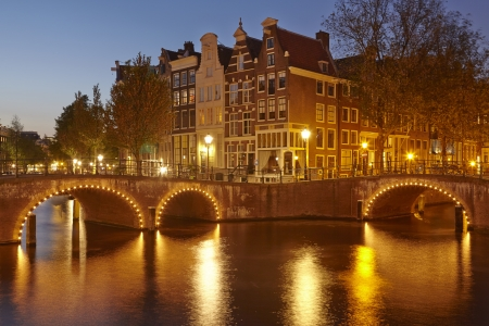 Arches of bridges and old houses at a canal in the evening  blue hour  in the capitol city of the Netherlands, Amsterdam