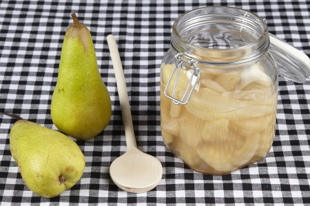 A bottling jar of cooked pears, a wooden spoon and raw pears are ready on a black and white checkered tablecloth.