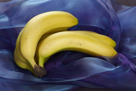 Some yellow bananas on a purple, marbleized background (like popart). Stock Photo