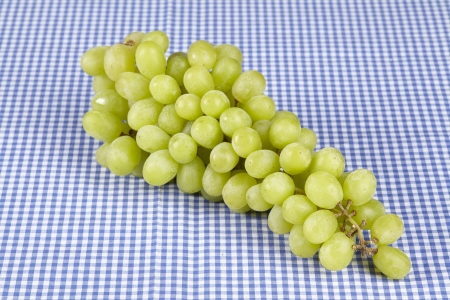 A bunch of grapes of a white type of grape on blue-white checkered tablecloth. Stock Photo