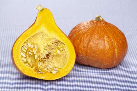 A half of a hokkaido pumpkin and a single pumpkin on a blue-white checkered tablecloth  Stock Photo