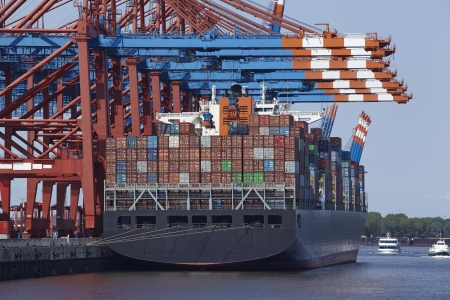containership: A container gantry crane loads or unloads a container ship with dozens of containers in different colors.