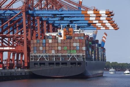 dozens: A container gantry crane loads or unloads a container ship with dozens of containers in different colors.