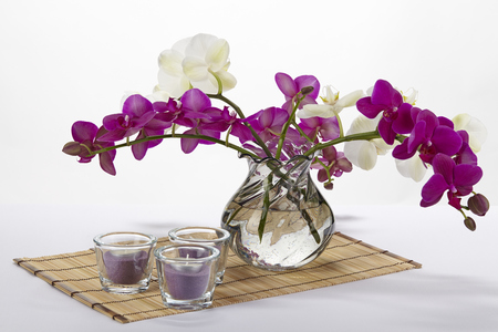 A bouquet of white and purple orchids in a vase  The vase is standing on a place mat made of bamboo