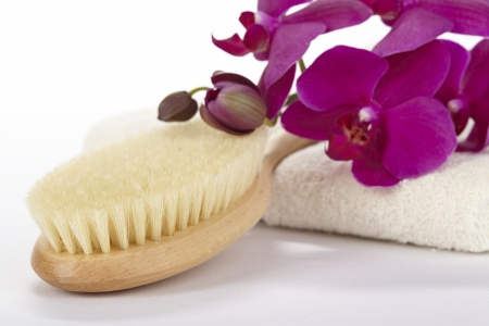 A bath brush is laying on folded, nature colored towel in front of a white background  The towel is decorated with a purple orchid