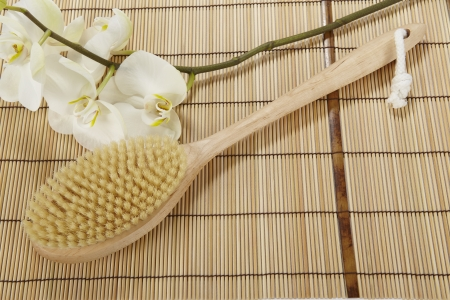 A bath brush is laying on a mat of bamboo  The decoration is made of a white orchid
