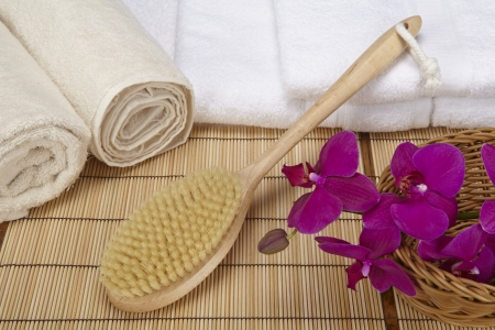 A bath brush is laying on a pile of white, folded towels  Beneath are two naturally colored, rolled towels and a basket with a purple orchid  Stock Photo