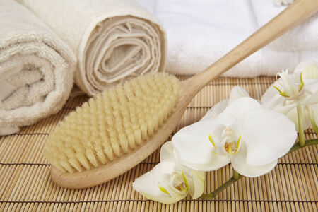 A bath brush is laying on a pile of white, folded towels  Beneath are two naturally colored, rolled towels and a white orchid  Stock Photo