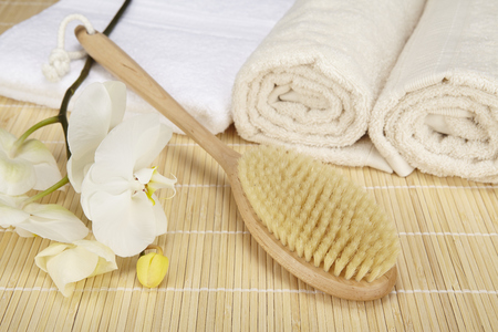 A bath brush is laying on a folded white towel on top of a bamboo mat. Beneath are two rolled naturally colored terry clothed towels. The scene is decorated with a white orchid.