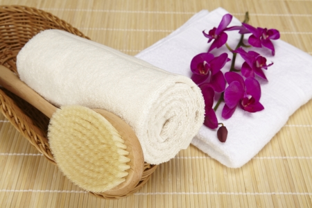 A bath brush and a rolled up terry clothed towel are laying into a basket. A folded white towel is located beneath the basket. The objects are standing on a bamboo mat (bath mat).  Stock Photo