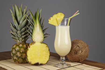 A Pina Colada, a half of a pineapple and a coconut are standiing on a tabletop of acacia wood. The background is gray.