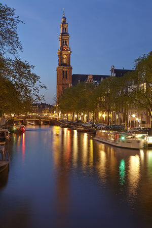 westerkerk: Canal and the Westerkerk (west church) in Amsterdam. The lights of some lanterns are refeflected in the water.