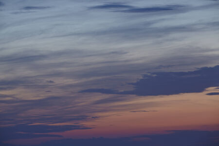Darker clouds in front of a colourful sky after sunset with many colours from yellow, red to blue. photo