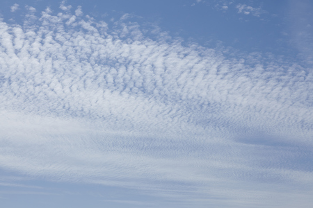 White high clouds in front of a blue sky with blurred contours photo