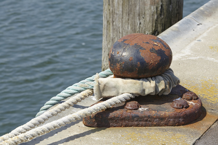 A bollard in a harbor with a thick rope to fasten a ship.