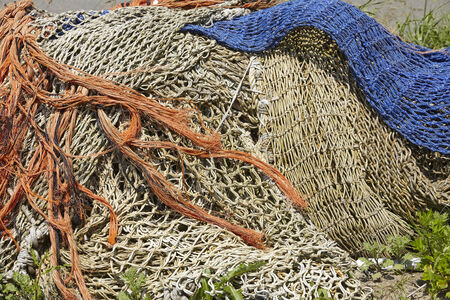 synthetic fiber: A pile of old fishing nets made of natural fibre and blue synthetic fiber are laying in the harbor.