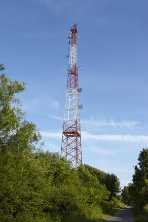 transmitting: A transmitting mast near Beldorf (Schleswig-Holstein, Germany) located at the Kiel Canal taken at a sunny evening with a blue sky.