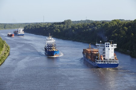 retouched: Some vessels at the Kiel Canal near Beldorf  Schleswig-Holstein, Germany  taken at daylight  All numbers and words on containers and ship are retouched in this image version