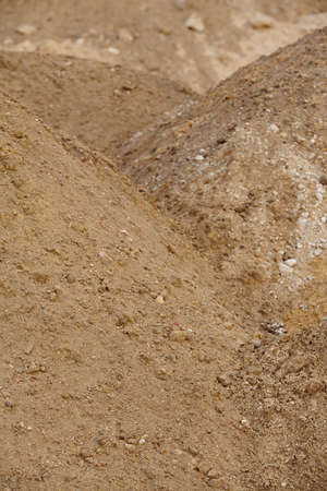 building material: A pile of building material from reddish and brownish sand and gravel. Stock Photo