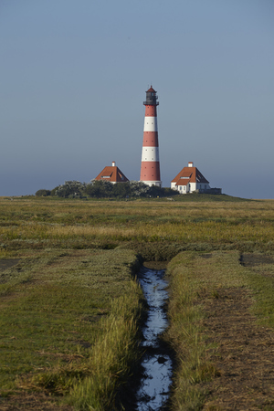 reflektion: Landscape with salt meadows anad the light house Westerhever located near the coast of the North Sea taken on a sunny morning. This landscape is located near the coast of the North Sea (North Frisia, Germany, Schleswig Holstein): Stock Photo