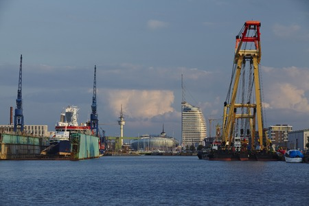 The inner city and skyline of Bremerhaven (Germany, federal state Bremen) taken from the harbour. In the foreground are some docks, ships, cranes and harbour installations. Editorial