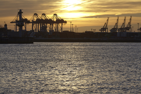 The Port of Hamburg with some container gantry cranes as silhouettes against the sun taken at sunset. photo