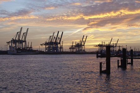 gantry: The Port of Hamburg (Germany) with container gantry cranes as silhouettes against a glowing orange yellow sky (sunset glow) taken on February 8, 2015.