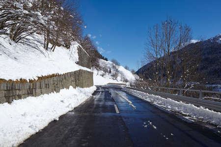 The Via S. Gottardo (road) at the Swiss canton Ticino (Tessin) taken in winter (February) with a bright blue sky and some snow near the St. Gotthard massif.