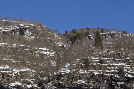 scarp: A mountain massif in the Swiss canton Ticino (Tessin) taken in winter (February) with some snow and a bright blue sky. Stock Photo