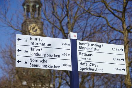 st pauli: The St. Michaelis Church (Michel) and a road sign to the Hafencity, Landungsbruecken (St. Pauli jetties), Jungfernstieg, Binnenalster, town hall, Tourist-Information and Speicherstadt (warehouse district) taken on March 8, 2015.