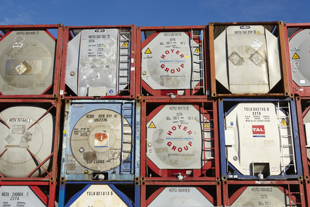 firms: A pile of tank container (tanktainer) of different haulage firms taken at the port of Hamburg against a bright blue sky on March 8, 2015.