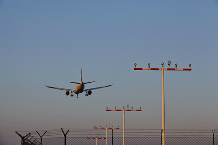 masts: A plane over some beaconing masts Approaches the airport of Frankfurt Main (Germany) in the evening on April 18, 2015. Editorial