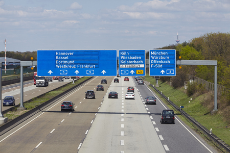 beneath: The federal Autobahn A5 beneath the Airport of Frankfurt (Germany) in direction to the Frankfurt Kreuz with a road sign to the airport taken on April 18, 2015.