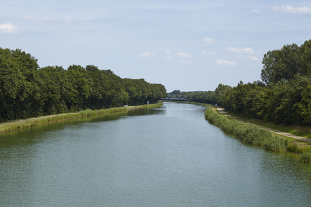 riverside trees: The Mittelland Canal at Bramsche (Germany, Lower Saxony) touches the horizon. Stock Photo