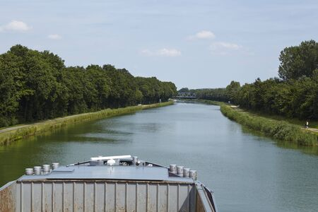 riverside trees: The Mittelland Canal at Bramsche (Germany, Lower Saxony) with the bow of an inland vessel.