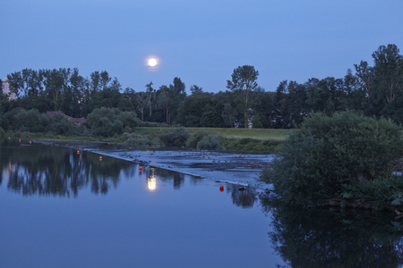 ruhr: The moonrise over the River Ruhr near Essen-Kray (Germany, Northrhine Westphalia) with the light of the moon reflecting in the water surface.