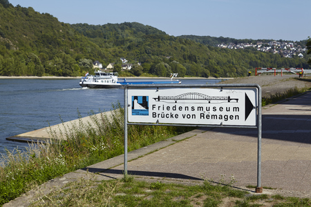 roadsign: A roadsign at the river Rhine points to Friedensmuseum (Museum of peace) The Remagen Bridge which was destroyed at the second world war (Germany, Rhineland-Palatinate, administrative district Ahrweiler).