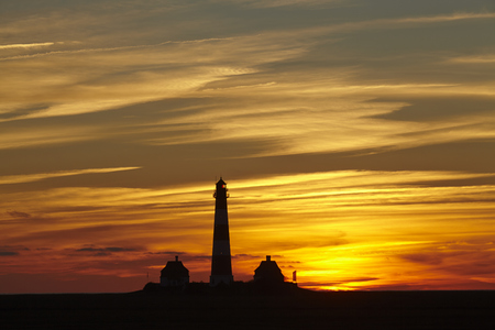schleswig holstein: The lighthouse Westerhever (Germany, Schleswig Holstein, North Frisia) photographed at a red sunset.