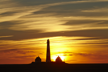 The lighthouse Westerhever (Germany, Schleswig Holstein, North Frisia) photographed at a red sunset.