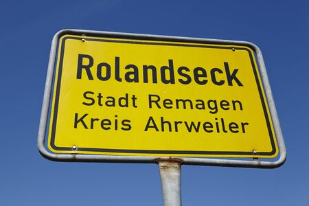 roadsign: A yellow town sign (roadsign) Rolandseck (City Remagen, administrative district Ahrweiler) photographed in front of a bright blue sky on August 31, 2015. Editorial