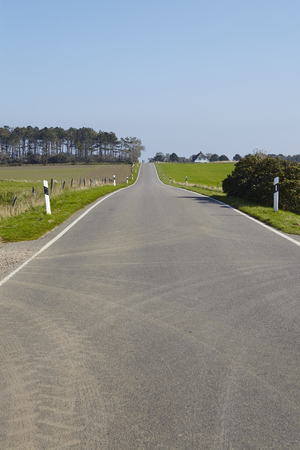 seemingly: A road leads seemingly to the horizon on the north frisian isle Amrum (Germany, Schleswig Holstien, North Frisia) and is photographed at sunny daylight and a bright blue sky.