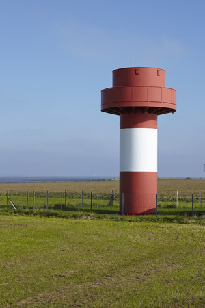 navigable: The small red-white ringed beacon fire is located in the south of the isle Amrum (Germany, Schleswig-Holstein, North Frisia). The lighthouse is the safety fuze of the navigable water Norderaue.