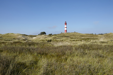 pharos: The red-white ringed lighthouse Amrum is built on top of a sand dune and is part of the community Nebel (Germany, Isle of Amrum, Schleswig-Holstein, North Frisia). Stock Photo